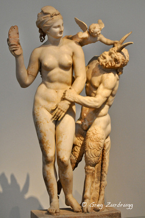 Aphrodite fending off Pan with her sandal, while Eros watches.